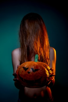 Halloween, femme en sous-vêtements avec citrouille dans ses mains. portrait sur mur vert foncé
