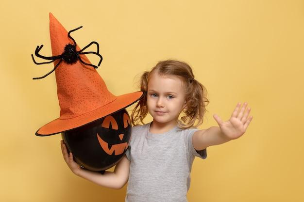 Halloween girl pose isolé tenir jack ballon effrayant visage citrouille main vide attention publicité