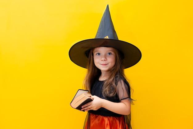 Halloween. une jolie fille sérieuse en costume de sorcière tient un vieux livre à la main. fond jaune coloré. un endroit pour le texte. photo de haute qualité