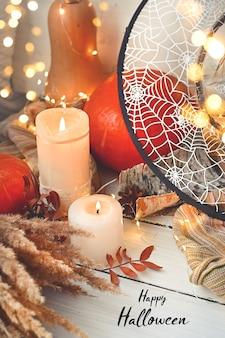 Halloween jour citrouille à côté de guirlandes lumineuses feuilles bougies magiques et chapeau de sorcière