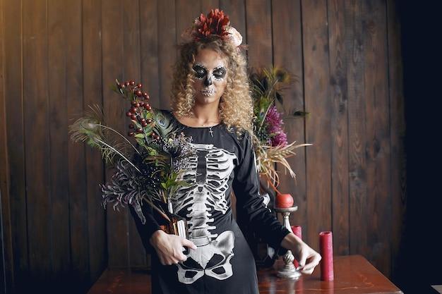 Halloween maquillage crâne belle femme avec une coiffure blonde. fille modèle santa muerte en costume noir.