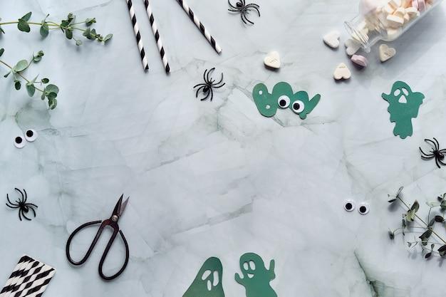 Halloween à plat avec de l'eucalyptus, des bonbons au sucre, des araignées en plastique noir, des ciseaux, une silhouette fantôme en papier, un mot boo et un espace de copie