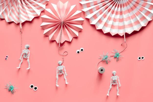 Halloween rose, vue de dessus. éventails en papier rayé, araignées, squelettes, yeux écarquillés sur papier rose.