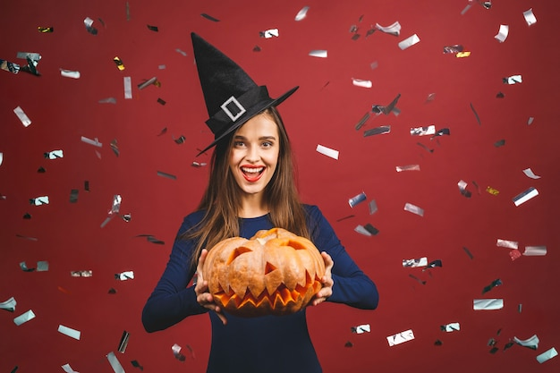 Halloween sorcière avec une citrouille sculptée - isolé sur fond rouge avec des confettis. émotionnelle jeune femme en costume d'halloween.