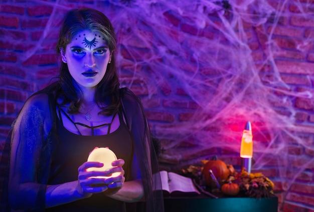Halloween sorcière, jeune femme déguisée en wicca tenant une boule magique sur toile d'araignée