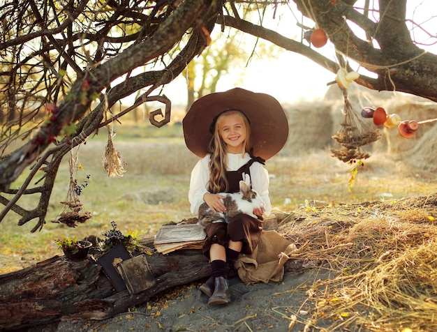 Halloween. sorcière joyeuse avec une baguette magique et un livre évoque et rit. petite fille en costume de sorcière