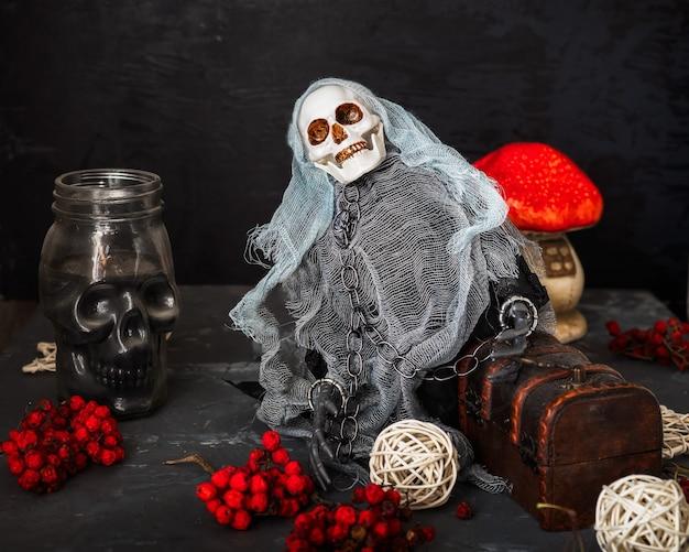 Halloween un squelette se trouve près d'un vieux coffre et d'une bougie avec des grappes de crâne