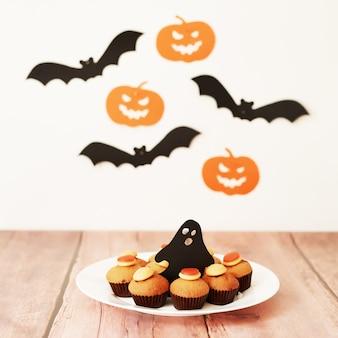 Halloween traite les petits gâteaux sur la table dans le contexte des citrouilles et des chauves-souris