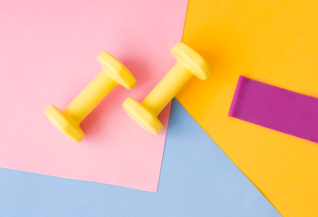 Haltère de couleur jaune sur tapis rose, bleu et jaune. conception d'une affiche ou d'une bannière de sport aux couleurs à la mode de 2021