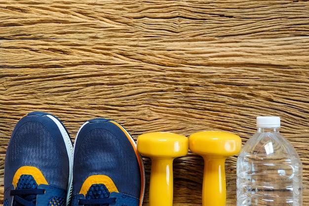 Haltère jaune avec des chaussures de sport et une bouteille d'eau.