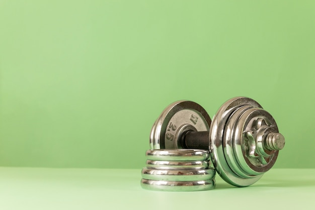 Haltère lourd professionnel avec crêpes sur fond vert. fond de concept de remise en forme ou de musculation.