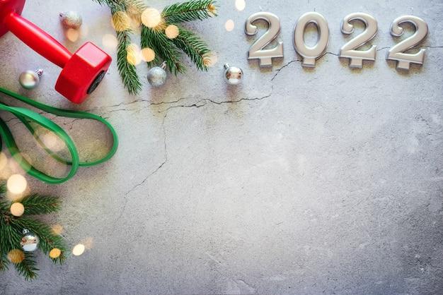 Haltère rouge, bande de résistance et accessoires de fitness sur fond festif du nouvel an