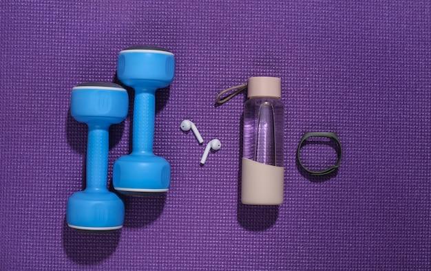 Haltères et accessoires de fitness sur un tapis de fitness. composition à plat