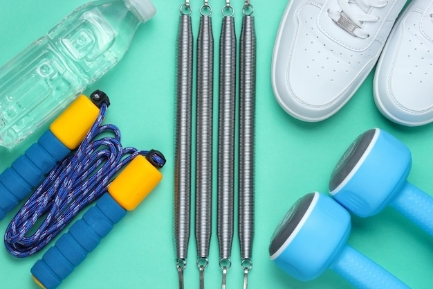 Haltères, baskets, corde à sauter, bouteille d'eau, extenseur. équipement de sport sur fond bleu. vue de dessus