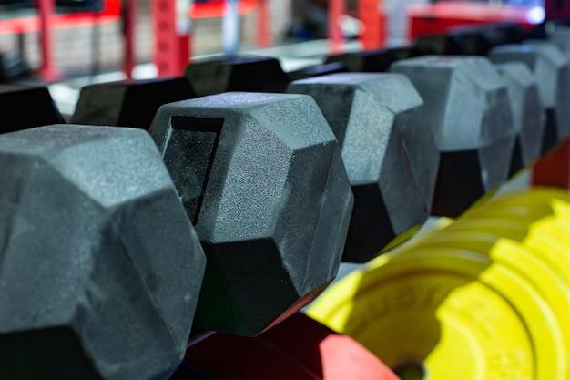 Haltères en caoutchouc noir. ensemble de poids lourds hexagonal utilisé pour les entraînements de gymnastique hardcore sérieux, l'entraînement cross fit et les routines d'entraînement