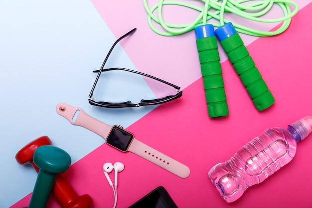 Haltères, corde à sauter, bracelet de fitness, eau et casque sur la couleur