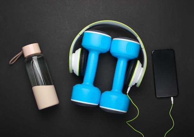 Haltères, écouteurs avec smartphone, bouteille d'eau sur surface noire