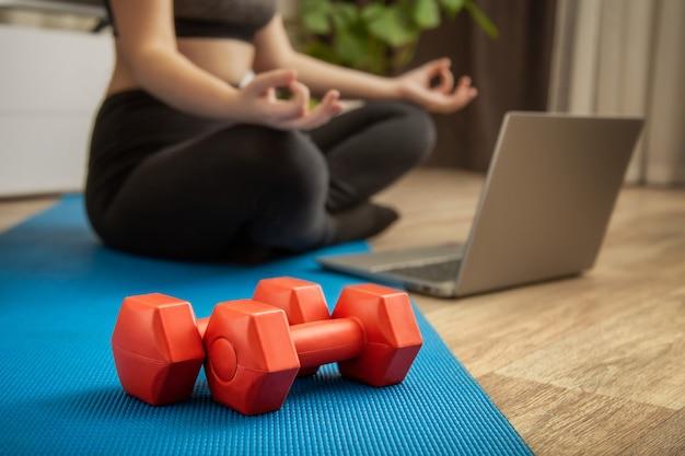 Haltères et femme sportive méconnaissable faisant de la méditation yoga fitness s'étirant à la maison via un ordinateur portable. jeune femme perdant du poids en faisant de l'exercice en ligne sur le sol de la maison. bien-être de la santé du corps.