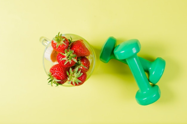 Haltères de fraise et de sport reposent sur une surface jaune clair