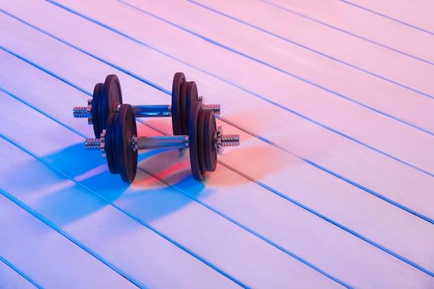 Haltères noirs sur plancher en bois avec néon rouge. matériel de fitness à domicile.
