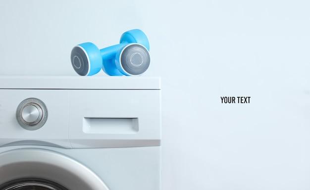 Haltères en plastique bleu sur machine à laver sur un fond blanc avec copie espace