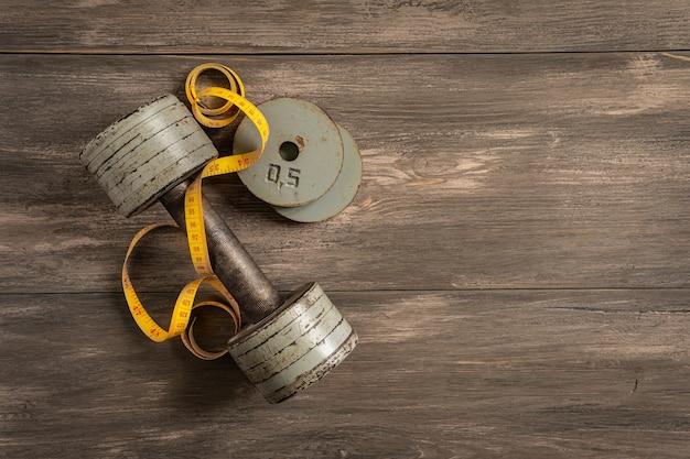 Haltères, roulette et ruban à mesurer sur un fond en bois