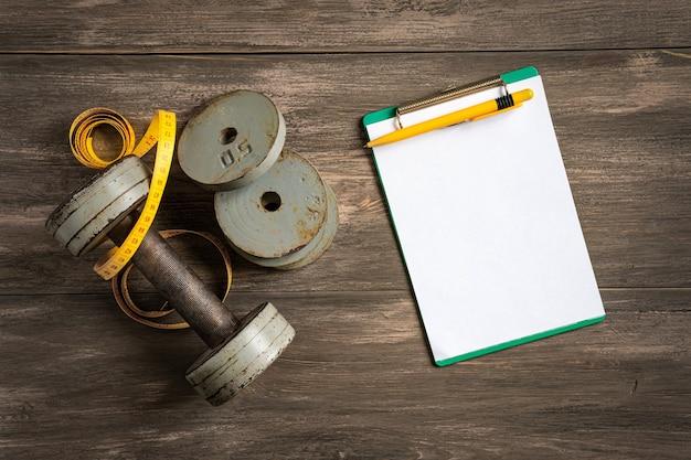 Haltères, ruban à mesurer et un cahier sur un fond en bois