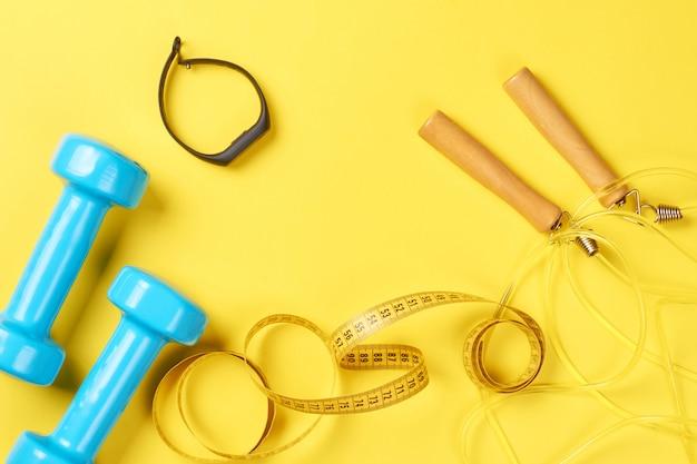 Haltères, traqueur de fitness, corde à sauter et ruban à mesurer sur fond jaune
