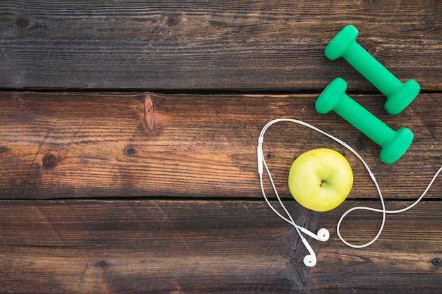 Haltères verts; écouteur pomme et blanc sur une planche en bois