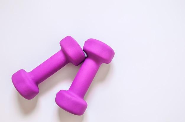 Haltères violettes, concept de conditionnement physique isolé sur fond blanc, concept de remise en forme isolé sur fond blanc, sport, body building. concept mode de vie sain, sport et alimentation. équipement de sport. copier l'espace