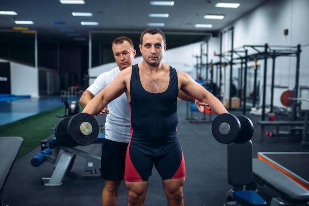 Haltérophile masculin faisant de l'exercice avec haltère sous le contrôle de l'entraîneur