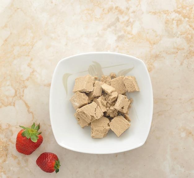 Halva dans une assiette avec des fraises sur une surface en marbre
