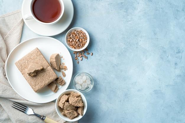 Halva avec graines et thé sur fond bleu clair. vue de dessus avec espace de copie. concept de dessert.