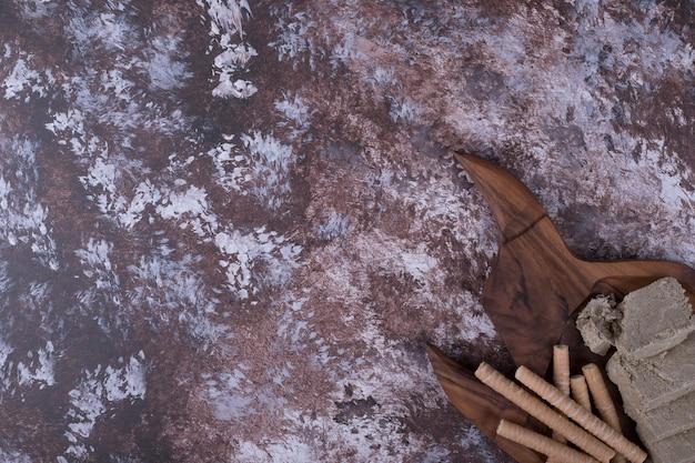 Halva de race blanche en tranches et servi avec des bâtonnets de gaufres dans un plateau en bois