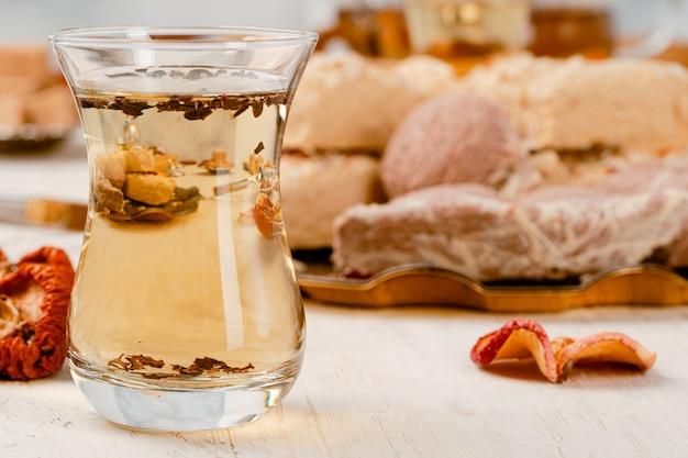 Halva turc avec du thé dans une tasse en verre se bouchent