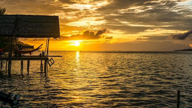 Hamac au coucher du soleil à la station de plongée - île de kri. stand up paddler sup. raja ampat, indonésie, papouasie occidentale