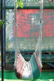 Un hamac fait de cordes est suspendu dans une zone de loisirs du pays.