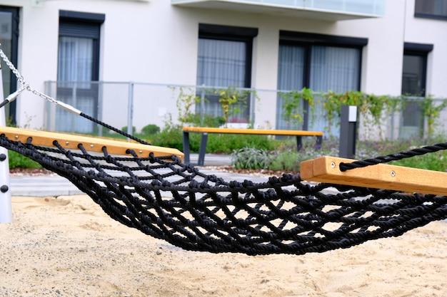 Hamac en gros plan sur un terrain de jeu dans une cour confortable du quartier résidentiel moderne.