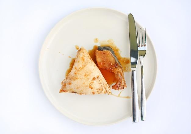 Hamachi cuit à la sauce teriyaki sur une plaque en céramique sur fond blanc.