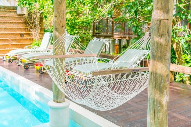 Des hamacs blancs dans la piscine de luxe.