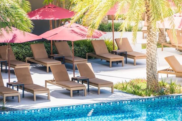 Hamacs placés dans une rangée à côté d'une piscine