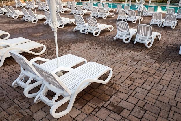Hamacs en plastique près de la piscine, vides d'ici la fin de la saison estivale.
