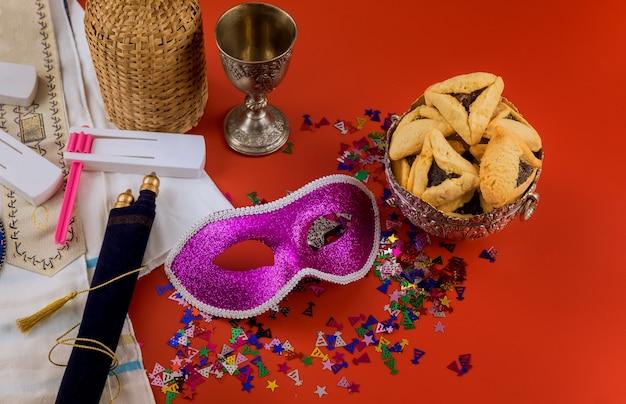 Hamans oreilles biscuits pour la célébration de la fête juive de pourim avec bruiteur et masque de carnaval de vin casher