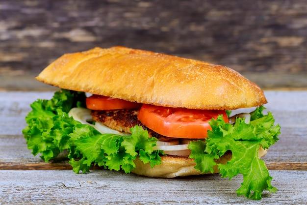 Hamburger appétissant avec frites, bière sur une planche à découper en bois.