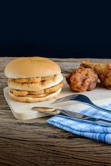Hamburger au poulet et poulet frit sur une planche à découper en bois