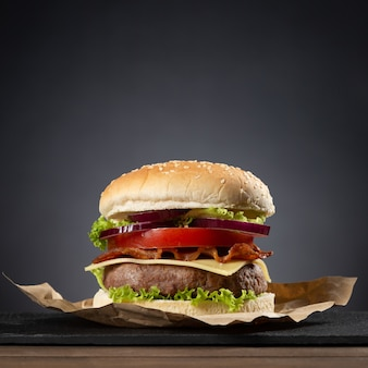 Hamburger sur base en bois sur fond noir