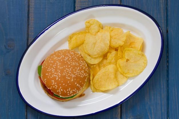 Hamburger avec des croustilles sur un plat blanc sur une table bleue