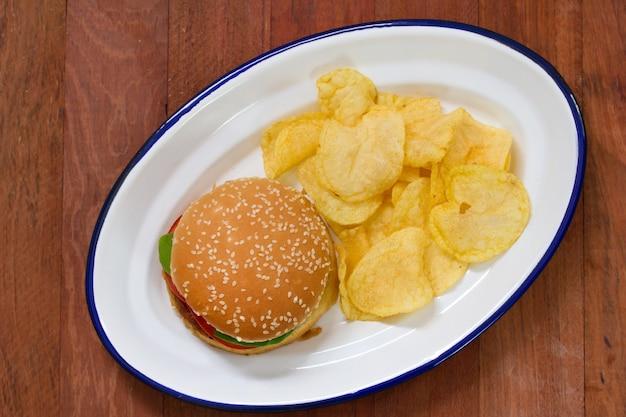 Hamburger avec des croustilles sur un plat blanc sur une table brune