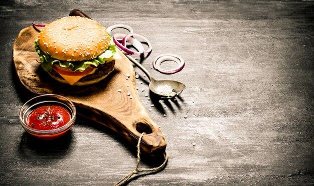 Hamburger cuit avec du ketchup et des rondelles d'oignon sur une planche en bois. sur un tableau noir.