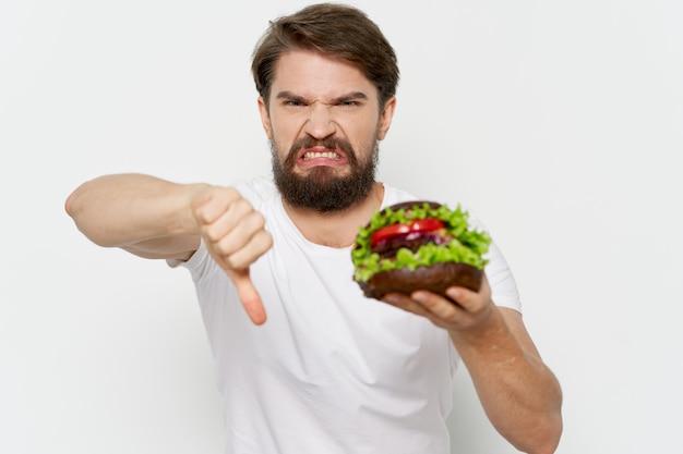 Hamburger dans les mains des hommes déplaisent le geste négatif avec la main de manger